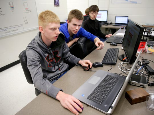 Parker Schroeder, a junior at Hortonville High School, Sam Schiedermayer, a freshman, and Ben Nowotny, an eighth-grader at Greenville Middle School, update code that will control their robot in preparation for the  FIRST Tech Challenge World Championships next week in St. Louis.