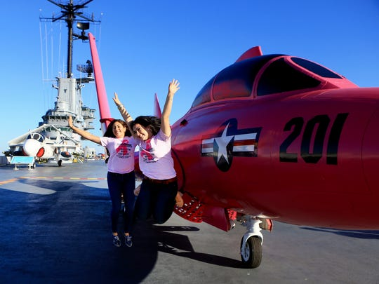 Brittany Ramirez (left) and Meagan Hatton jump as they get their photo taken next to a pink F9F-8 Cougar after it was loaded to the USS Lexington flight deck in support of Breast Cancer Awareness on Oct. 17, 2016, at the USS Lexington Museum on The Bay in Corpus Christi.
