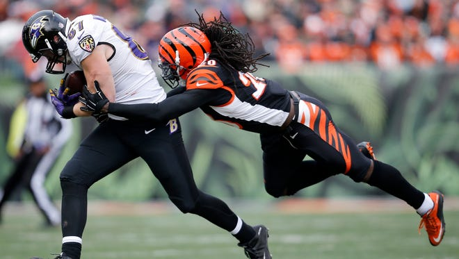 Baltimore Ravens tight end Konrad Reuland (86) is brought down by Cincinnati Bengals free safety Reggie Nelson (20) in the second quarter of the NFL Week 17 game between the Cincinnati Bengals and the Baltimore Ravens at Paul Brown Stadium in downtown Cincinnati on Sunday, Jan. 3, 2016. At the half, Baltimore led Cincinnati 9-7.