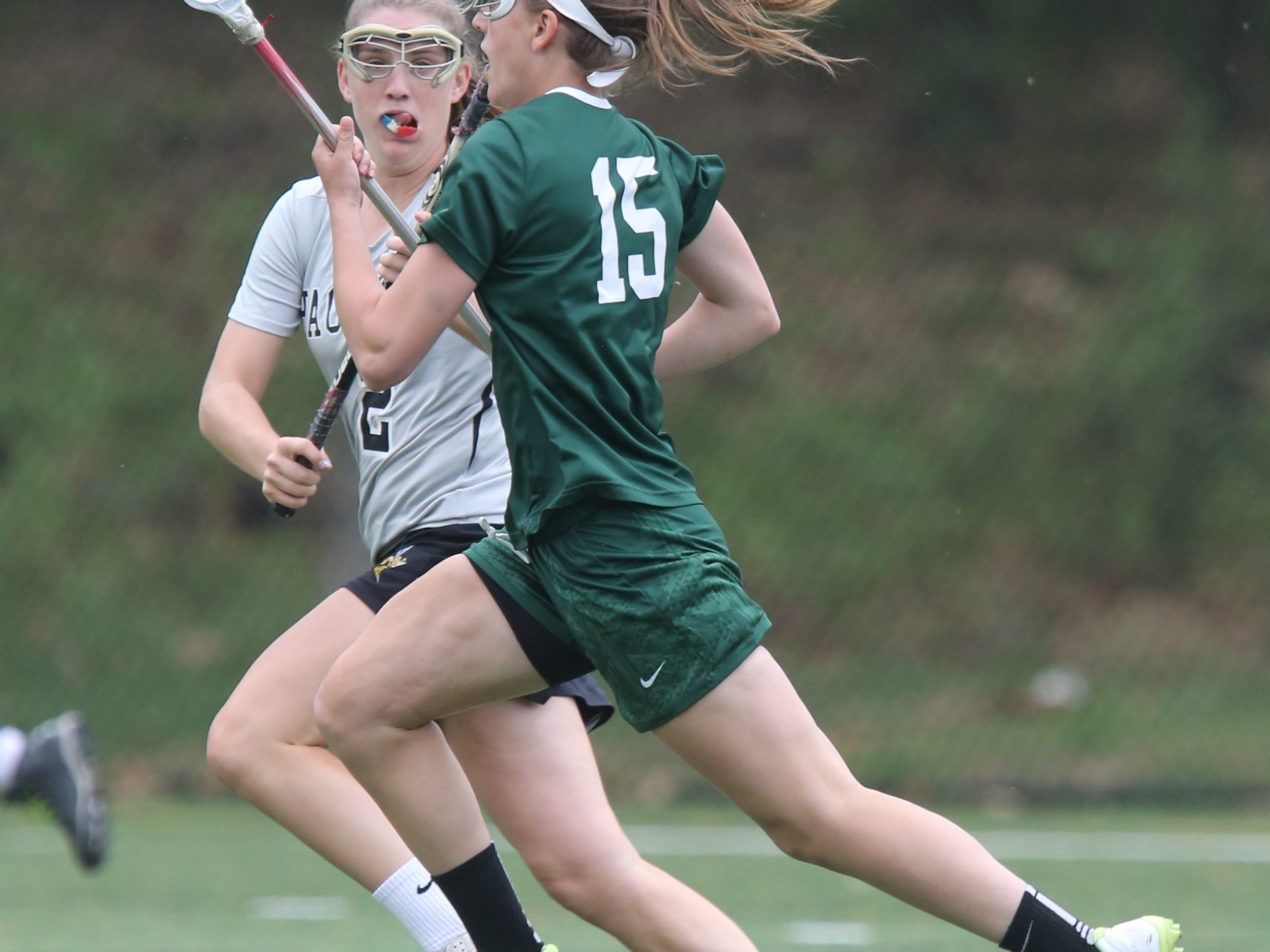 Hackley's Sammy Mueller (2) guards Yorktown's Ashley Stilo (15) as she carries the ball up the field during girls lacrosse action in Tarrytown on May 12, 2015. Yorktown defeated Hackley 11-5.