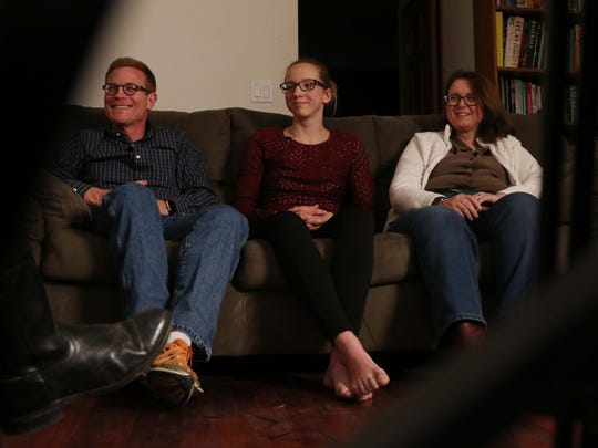 Olivia Jenks, sophomore at Ames High School sits between her parents, William and Cynthia while talking about her brother Timothy Jenks on Sunday, April 10, 2016, in Ames. Timothy was killed in a biking accident in June 2014 while the twins were training for a triathlon.