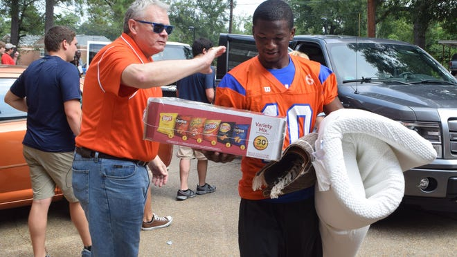 Louisiana College president Dr. Rick Brewer (left) pats LC Wildcats football player Farron Jones (right) on the back as he and his teammates help students move items into Cottingham Hall on the Louisiana College campus Saturday.