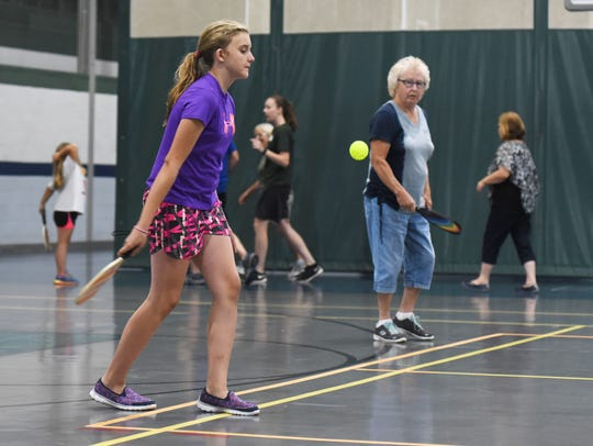 Ally Blevins, 12, serves while playing pickleball with