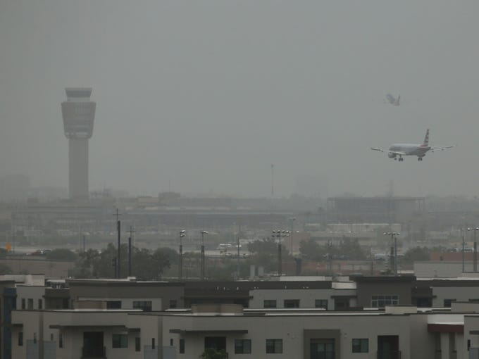 Passenger jets land and take-off in the dust at Sky