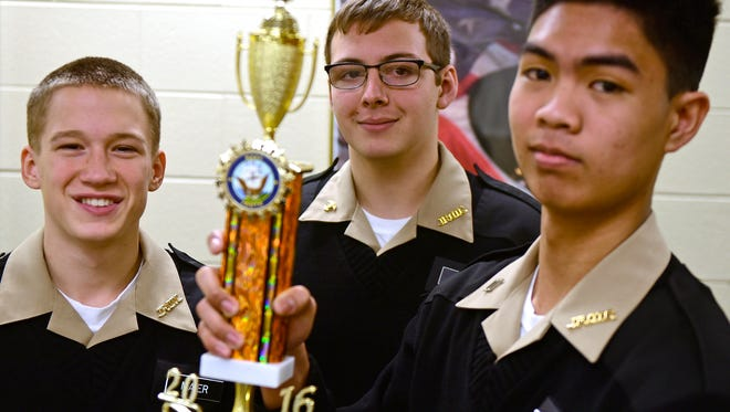 Chambersburg Area Senior High School JROTC Naval cadets Owen Maier, left, Isaac Hull and Rainmar Leguarda hoists a trophy they won during regional competition. A team of student won first place during the 29th Annual Martin Luther King Jr. Regional Drill Meet Varsity Academic Challenge.