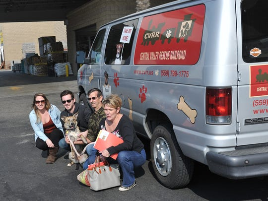 A family poses with the dog they just adopted at a Central Valley Rescue Railroad adoption event at PetSmart in Visalia on Feb. 13, 2016.