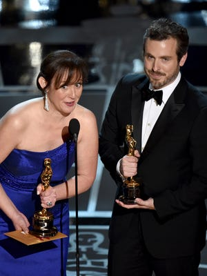 """Kristina Reed, left, and Patrick Osborne accept the award for best animated short film for """"Feast"""" at the Oscars on Sunday, Feb. 22, 2015, at the Dolby Theatre in Los Angeles."""