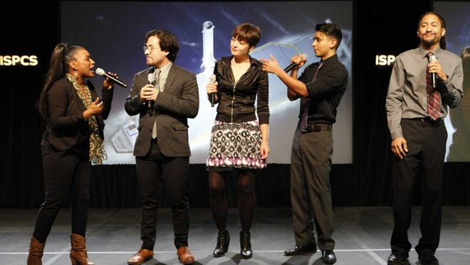 """Megan McQueen, center, and New Mexico State University music theater students perform a song from the Broadway musical """"Hamilton"""" at the International Symposium on Personal and Commercial Spaceflight in Las Cruces in October 2017."""