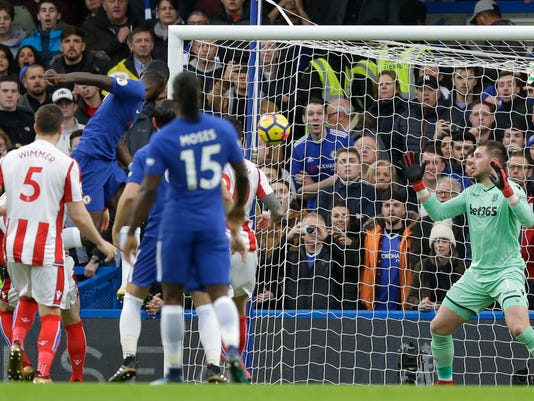 Chelsea's Antonio Rudiger, top left, heads the ball and scores his side's first goal during their English Premier League soccer match between Chelsea and Stoke City in London, Saturday, Dec. 30, 2017. (AP Photo/Alastair Grant)