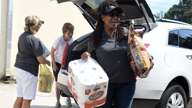 Volunteer Sonya Oatis carries donated supplies for Harvey victims on Tuesday. Midtown Market collected supplies Tuesday and will deliver them to those impacted by Harvey. A truck was parked by Tabella from 8 a.m.-6 p.m. to collect supplies.