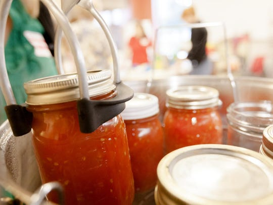 Filled jars of crushed tomatoes ready to be heated