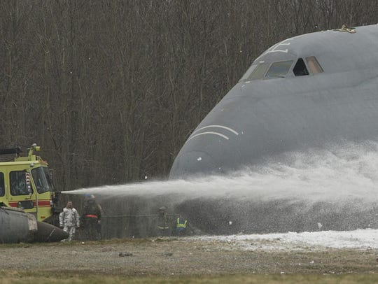 Firefighters spray foam to a downed military C5 Galaxy