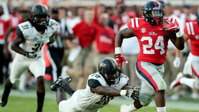 Ole Miss running back Eric Swinney (24) pulls away from a Vanderbilt defender for a 55-yard touchdown in the second half on Saturday. The Rebels won 57-35.