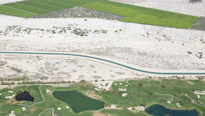 Water from the Colorado River flows through the Coachella branch of the All-American Canal, running alongside farmland, a golf course and the desert in the eastern Coachella Valley.