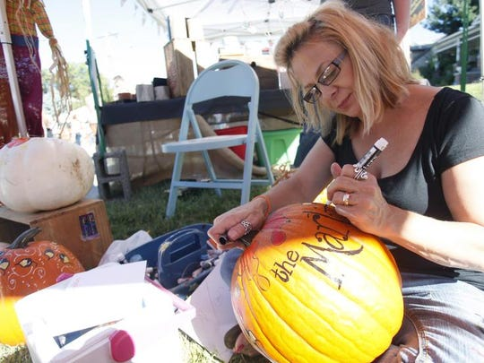 Mary Guccione decorates a pumpkin in her booth, The Funky Pumpkin, during last year's Cider Days on historic Walnut Street.