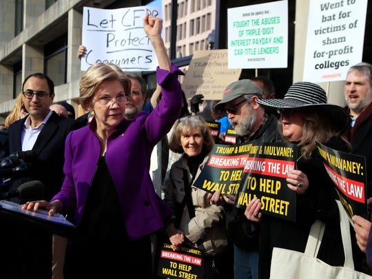 Sen. Elizabeth Warren, D-Mass., joins a rally outside the Consumer Financial Protection Bureau headquarters in Washington, Tuesday, Nov. 28, 2017. The group was protesting President Donald Trump's appointment of Mick Mulvaney as Consumer Financial Protection Bureau's acting director.