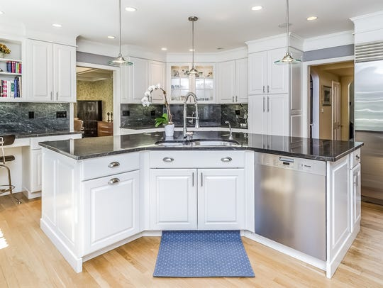 The kitchen offers an expansive granite stone center island and stainless steel appliances.