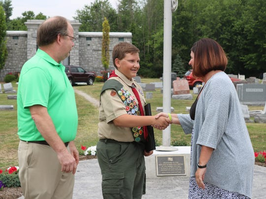 Councilwoman Lisa Sarty and Mayor Hugh Wheeler congratulate Jayce Kennedy as he reached the rank of Eagle Scout with a project to revitalize Lakeview Cemetery's veterans' memorial.