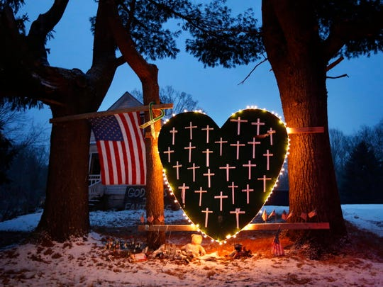 In this Dec. 14, 2013, file photo, a makeshift memorial with crosses for the victims of the Sandy Hook Elementary School shooting massacre stands outside a home in Newtown, Conn., on the one-year anniversary of the shootings.