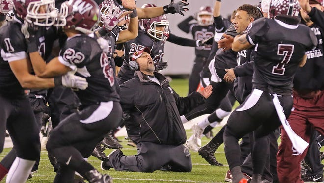 Wayne Hills coaches and players celebrates their overtime win after a fumble rolled out of the end zone giving Wayne Hills the ball and the win in December.