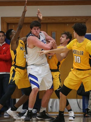 Covington Catholic's Jake Walter tries to protect the ball from Moeller defenders during their game at CovCath, Tuesday, December 12, 2017.