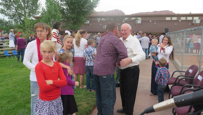 Dan Barlow, Colorado City's first mayor, in white shirt, hugs a visitor at Cottonwood Elementary School during last year's Fourth of July celebrations.