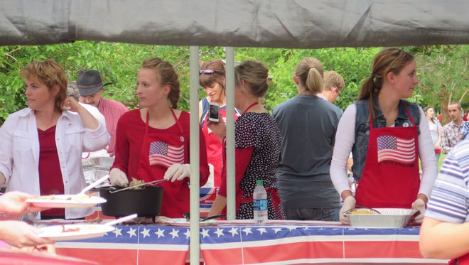 Women serving breakfast at Colorado City's 2015 Fourth of July celebration chat with visitors at Cottonwood Park.