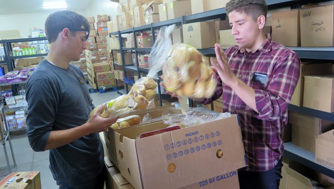 Alex Johns, left, and Sam Peterson, missionaries with The Church of Jesus Christ of Latter-day Saints, were connected through the JustServe program to do volunteer work at the SwitchPoint food pantry in St. George Friday, Sept. 4, 2015.