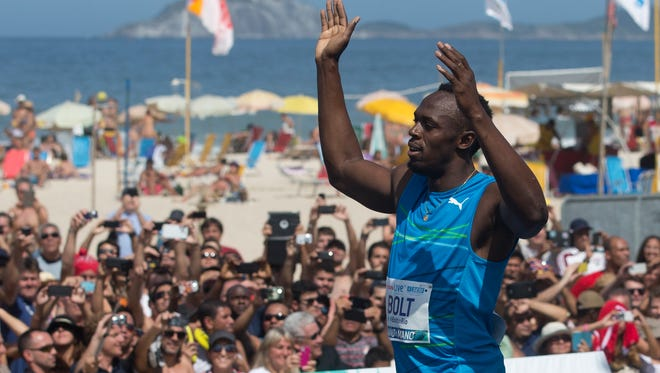 """Jamaican Olympic gold medallist Usain Bolt celebrates after winning the """"Mano a Mano"""" men's 100 challenge in Rio de Janeiro, Brazil, Sunday, Aug. 17, 2014."""