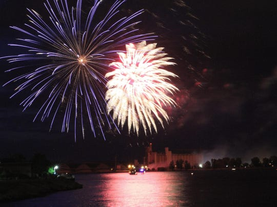 Fireworks fill the sky with color and reflect off the St. Clair River.