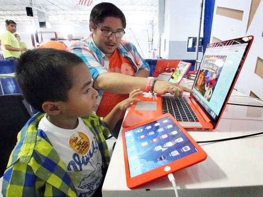 Felix Salcido, 4, is helped by his father, Ricardo Herrera as he watches a program via computer and iPad in a PBS table at the 2015 PBS Kids Fiesta.