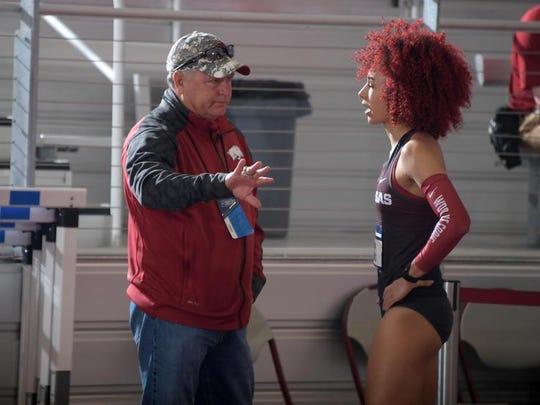 Arkansas Razorbacks assistant coach Bryan Compton (left) talks with Taliyah Brooks during the pentathlon high jump.