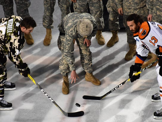 A soldier drops the puck in a ceremony before the Hershey
