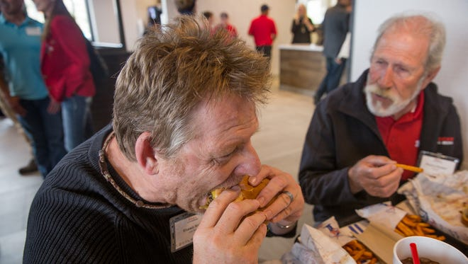 Shawn Kelly, left, takes a bite out of his hamburger as Rosco Hooper enjoys his fries Thursday at the new Blake's Lotaburger location in Farmington.