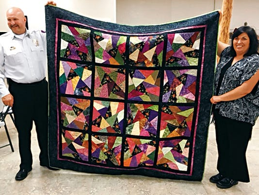 Fire Chief Harlan Vincent and Fire Department Office Manager Elaine Reynolds show off the quilt made by the Stash Sisters for the fire department's annual fund raiser.