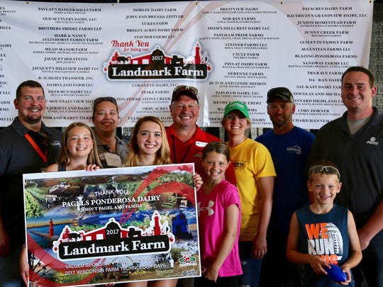 The Pagel family receives recognition during the 2017 Farm Technology Days as one of the Landmark Farms in Kewaunee County. Front row (from left)  Brooke Witcpalek, Kiley Pagel, Braelyn Witcpalek, and Brex Witcpalek. Back row (from left) JJ Pagel, Chase Pagel, John Pagel, Jamie Witcpalek, Steve Witcpalek, and NAPA rep Logan Bosar from Ball Auto and Truck Parts.