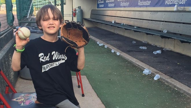Lucas Andreatta, 6, son of D&C Columnist David Andreatta, shows off his baseball mitt and found baseball in the Rochester Red Wings dugout on May 3, 2015.