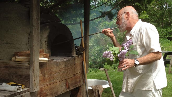 Richard Fink, co-owner of Ariel's Restaurant and Cantina, at the wood-fired oven in his backyard, which is also the restaurant's backyard. He holds freshly picked lilacs for the tables.