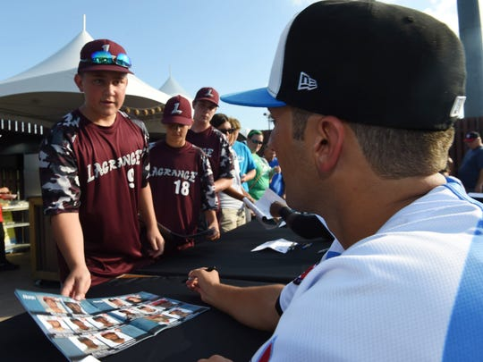 LaGrange little league player Matt Zipser hands his program to Hudson Valley Renegade Joe Serrapica during an autograph session prior to the start of the New York Penn League All Star Game at Dutchess Stadium on Tuesday.