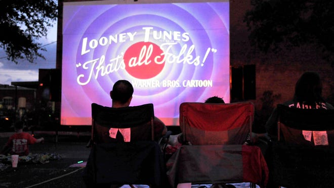 Downtown Movie Night patrons relax on blankets, pillows and folding chairs, watching Looney Tunes cartoons before the feature presentation begins in 2015.
