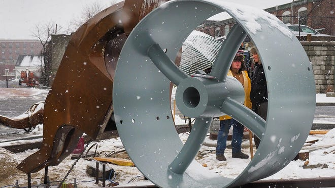 """In this November 2018 photo, the hammer of struggle is attached to a pulley wheel like the ones made by the Portsmouth Machine Co. in the 1800s as part of the sculpture """"Hammer-Heads"""" in a roundabout at the city's new Foundry Place Garage."""