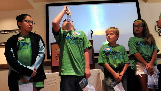 Connor Karl, 10, tilts his head back to demonstrate the use of an inhaler while Shelby Moreno, 10 (left), Samuel Seigler, 10, and Alyssa Hernandez, 11, watch Thursday, July 6, 2017. All four kids took their turn demonstrating the device for benefit of the other 30 children at the Hendrick Kick Asthma Primetime Fun Day. The day camp taught children how to recognize the triggers for their asthma and ways for managing their condition.
