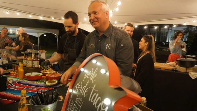 John Rivers, entrepreneur of 4Rivers Smokehouse, serves his community at the Pink and Swine event.