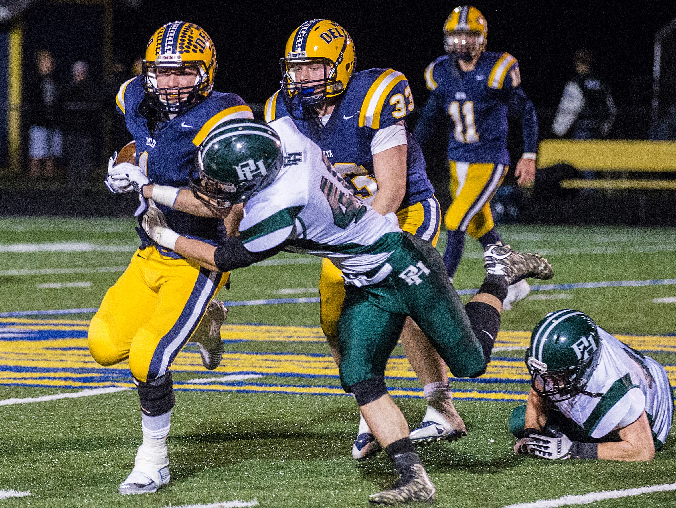 Delta's Zach Mills fights past Pendleton Heights' defense during their game at Delta High School Friday, Nov. 6, 2015.