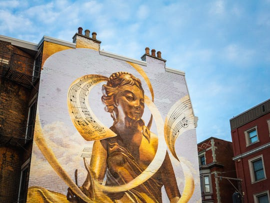 """""""The Golden Muse"""" mural at the corner of West 13th Street and Race Street was designed by artist Tim Parsley. The figurine is wrapped in the notes of Aaron Copland's """"Fanfare for the Common Man."""" This ArtWorks project debuted in 2012."""