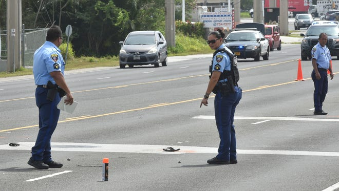 Guam Police Department officers process the scene of an auto-pedestrian fatality near the Mangilao Pay-Less Supermarket on April 7. The pedestrian was rushed to Naval Hospital Guam where she was pronounced dead at 9:35 a.m., said GPD Officer Paul Tapao, acting spokesman.
