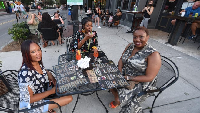 Shanna Hooper, from left, Shay Spencer and Sonya Caldwell eat a table at Bourbon St. during Downtown Alive in Wilmington, N.C., Saturday, July 18, 2020. The initiative began on June 23 to help businesses add outdoor space to help alleviate the loss of indoor space caused by coronavirus restrictions. The blocks include Front St between Chestnut and Dock, and the 100 block of Princess St. It runs on Thursday and Friday from 6:30 p.m. to 10 p.m., Saturdays from 10 a.m. to 10 p.m., and Sundays from 10 a.m. to 5 p.m. through Sept. 7.