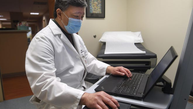 Dr. Paul Kamitsuka makes notes between seeing patients Friday at Wilmington Health, where he is an infectious-disease specialist. Kamitsuka also has serves as chief epidemiologist at New Hanover Regional Medical Center.
