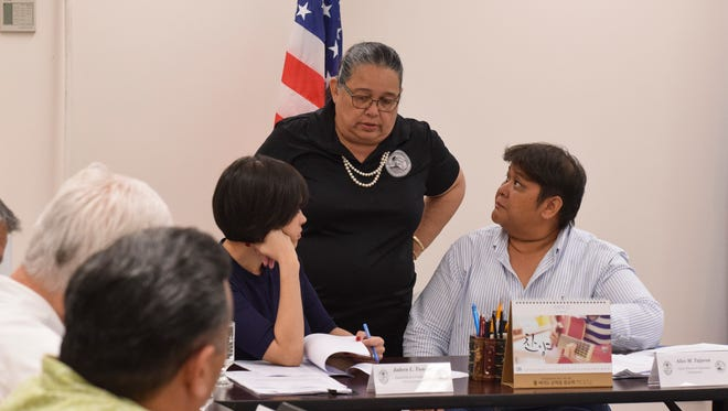 Guam Election Commission Ex-Officio Secretary Maria I.D. Pangelinan, center, confers with Vice Chairperson Jadeen L. Tuncap, left, and Chairperson Alice M. Taijeron before their board meeting in Hagåtña on June 30, 2018.