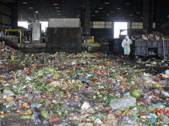 A worker walks through yard and food waste at the Material Recovery Facility in Fontana, July 28, 2015.